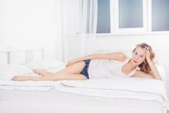 性感的妇女在牛仔布短裤和白色躺穿戴了在床上 免版税库存图片