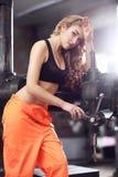 性感的妇女在运转在工厂的钻子机器旁边的橙色制服weared 免版税图库摄影