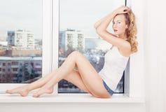 性感的妇女在说谎在窗口附近的牛仔布短裤和白色穿戴了 免版税库存照片