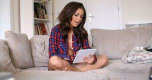 性感的妇女坐有片剂计算机的长沙发 影视素材