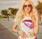 年轻性感的妇女夏天画象葡萄酒T恤杉的,红色摆在加利福尼亚的短裤和太阳镜靠岸 库存照片