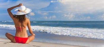 性感的妇女女孩太阳帽子&比基尼泳装坐海滩 库存图片