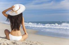 性感的妇女女孩太阳帽子&比基尼泳装坐海滩 免版税库存照片