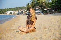 年轻性感的妇女安置和变柔和近,在暑假好热的天团结,穿在热带的一件黑汗衫 免版税图库摄影