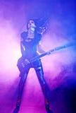 性感的妇女弹吉他在音乐会 免版税库存照片