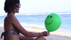 年轻性感的妇女快乐地坐与绿色气球的海滩 巴厘岛印度尼西亚 充分的HD, 50fps 在海洋附近 股票视频