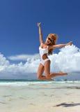 性感的妇女愉快跳跃的放松在热带海滩送 图库摄影