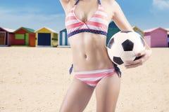 性感的妇女拿着一个足球 库存图片
