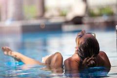 性感的妇女放松的躺下在豪华游泳池 库存图片