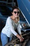 性感的妇女检查汽车 免版税库存图片