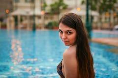 性感的妇女画象坐游泳池,佩带的比基尼泳装边缘,当在度假在晴朗的热带目的地时的 免版税图库摄影
