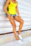 年轻性感的妇女的长的美好的被晒黑的亭亭玉立的腿蓝色deni的 免版税图库摄影