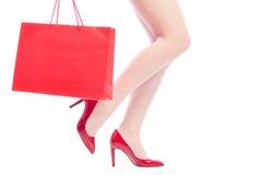 性感的妇女腿、红色鞋子和购物袋 图库摄影