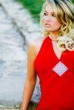 性感的妇女-在正式红色礼服的白肤金发的模型 免版税库存图片