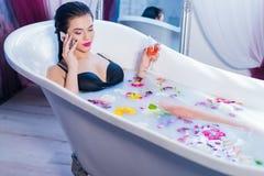 性感的妇女说在电话里,当洗浴时 库存图片
