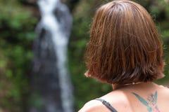 年轻性感的妇女画象热带巴厘岛,印度尼西亚雨林的  在背景的瀑布 罕见的看法 库存照片