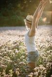 性感的少妇享用太阳室外在花田 免版税库存图片