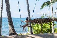性感的少妇坐在热带海滩的摇摆,天堂海岛巴厘岛,印度尼西亚 晴天,愉快的假期 图库摄影
