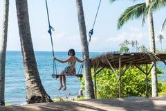 性感的少妇坐在热带海滩的摇摆,天堂海岛巴厘岛,印度尼西亚 晴天,愉快的假期 库存照片