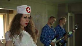 性感的少妇护士在精神病院唱歌,尖叫,与疯狂的患者的呼喊 疯狂的吉他弹奏者执行与 股票录像