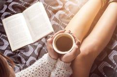 性感的少妇细节和太阳点燃 妇女保留一个咖啡杯并且读了书 库存照片