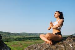 性感的少妇画象sporrtswear实践的瑜伽的在峭壁 绿色山风景背景 库存图片