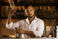 性感的年轻人疯狂配制饮料为他的客人做准备 免版税库存图片