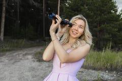 性感的年轻金发碧眼的女人看某事通过范围 库存照片