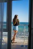 性感的式样妇女在有海的阳台站立背景的 图库摄影