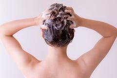 性感的式样按摩的香波到她的头发里,从后面的特写镜头外形 图库摄影