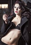 性感的抽烟的荡妇妇女特写镜头画象内衣和外套的 图库摄影