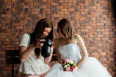 年轻性感的摄影师显示新娘拍了照片 免版税库存图片