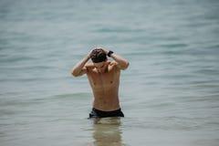 性感的摆在一个海滩的白种人适合的人在水中 免版税库存照片