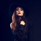 性感的摆在黑衬衣和典雅的帽子的魅力女性模型 免版税库存照片