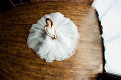 性感的新娘在演播室坐木地板 库存图片