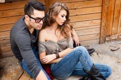 性感的时兴的夫妇佩带的牛仔裤摆在剧烈 免版税库存照片