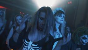 性感的最基本的衣服和面孔油漆跳舞的女孩在人群在万圣夜集会 股票录像