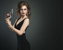 性感的有枪的秀丽少妇在一张黑暗的bg画象 库存照片