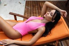 性感的桃红色泳装的美丽的女孩在sunbed 库存照片