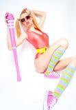 性感的棒球女孩佩带的colorfull给摆在与棒球棒穿衣 免版税库存照片