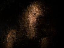 性感的模型光滑的画象,摆在透明玻璃复盖后由水滴下 年轻忧郁和哀伤的妇女 图库摄影