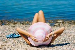 性感的比基尼泳装妇女晒黑的放松在海滩 从躺下与草帽的后面的晒日光浴无法认出的女性的成人下 图库摄影