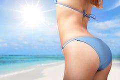 性感的比基尼泳装的少妇在海滩 库存图片