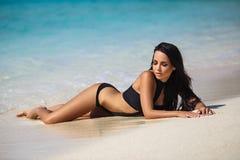 性感的比基尼泳装的美丽的女孩在海滩 库存照片
