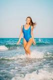性感的比基尼泳装身体妇女嬉戏在获得天堂热带的海滩使用的乐趣飞溅水 美好的豪华的t适合女孩 免版税库存照片