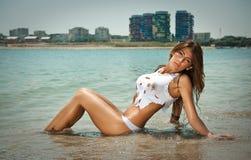 年轻性感的深色的女孩画象白色比基尼泳装和湿T恤杉的在海滩 库存照片