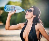 年轻性感的深色的女孩画象黑低胸的泳装饮用水的从瓶 肉欲的可爱的妇女 免版税库存照片