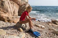 性感的潜水者女孩坐多岩石的海滩和预习功课的峭壁 库存照片
