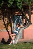 性感的牛仔布短裤和太阳镜的时兴的少妇 性感 免版税库存照片