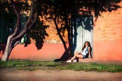 性感的牛仔布短裤和太阳镜的时兴的少妇 Pla 库存照片